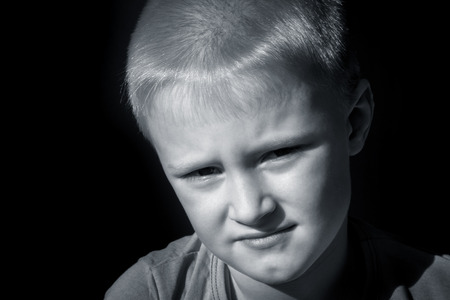 Upset abused frightened little child (boy),  close up horizontal dark portrait with copy space photo