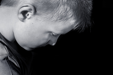 Upset abused frightened little child (boy),  close up horizontal dark portrait with copy space Stock Photo
