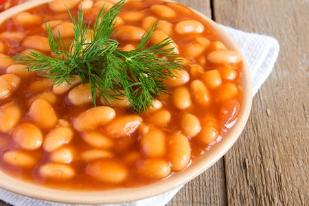 ejotes: Frijoles en sause tomate con eneldo sobre fondo de madera, de cerca horizontal
