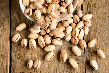 rustic food: Salty pistachios nuts in bowl on rustic wooden background, close up, horizontal, copy space, vegetarian food