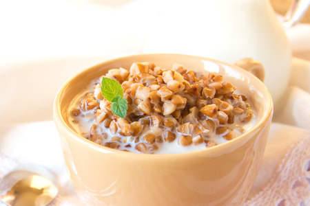 Buckweat porridge with milk and mint on white napkin, close up, horizontal. Natural organic vegetarian food (breakfast). photo