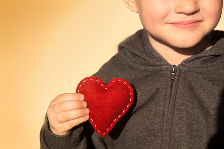 Red heart in child hands. Kindness concept, gift, hand made valentine, close up, horizontal, copy space