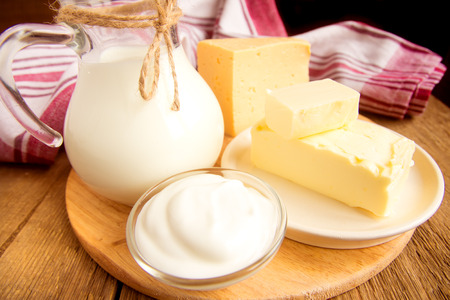 Dairy products - milk, cheese, butter, sour cream over wooden table