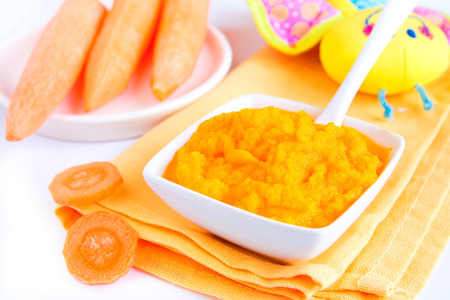 pureed: Baby food (pureed carrot) close up on white table