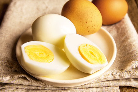 Boiled eggs over rustic linen and wooden background