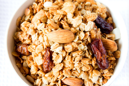 musli: Wholegrain musli (granola) close up texture with raisin, dry fruits, nuts and cereals. Healthy food.