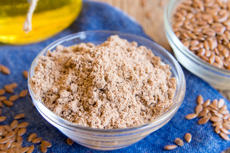 Flax powder and seeds in bowl close up