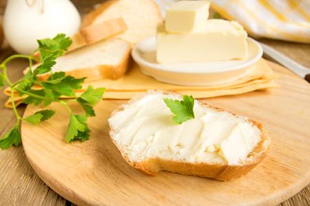 mantequilla: Mantequilla y pan para el desayuno, con perejil sobre mesa de madera Foto de archivo