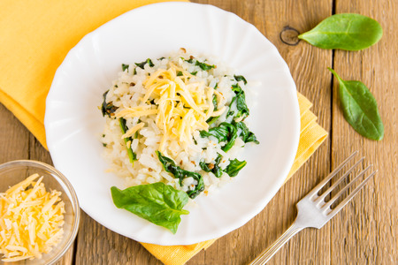 rice plate: Spinach risotto with white rice and grated cheese on plate, italian vegetarian cuisine, close up, top view Stock Photo