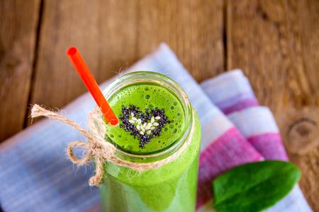 batidos frutas: Vegetal verde y hierbas Smoothie con corazón de semillas de amapola y sésamo. El amor por un concepto de alimentos crudos saludable.