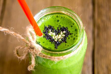 Groene groente en kruiden smoothie met hart van papaver en sesamzaad. Liefde voor een gezonde voeding concept rauw.