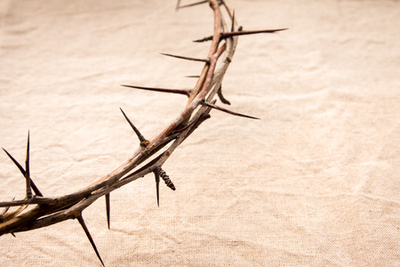 persecution: Crown of thorns over old fabric background, religious concept Stock Photo