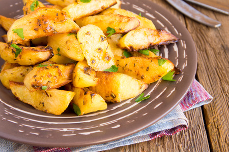 Homemade baked potatoes with spices and herbs on plate over rustic wooden background close up photo