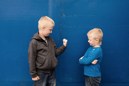 anger kid: fight between two brothers (kids, boys), angry aggressive children Stock Photo