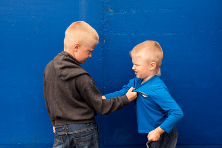 bad behavior: children fight between two angry aggressive brothers (kids, boys)