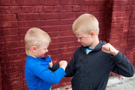 peleando: niños se pelean entre dos hermanos agresivos enojados (niños, muchachos) Foto de archivo