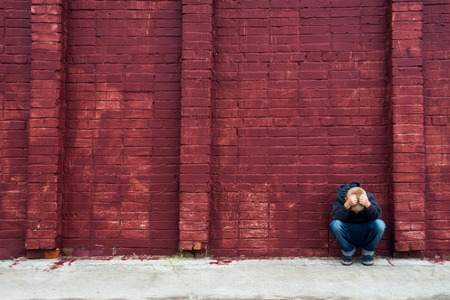 Depressed abused upset crying child (boy, kid, teen) sitting near red brick wall 版權商用圖片