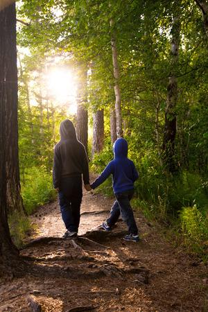 Children walking, hiking in wild green summer forest
