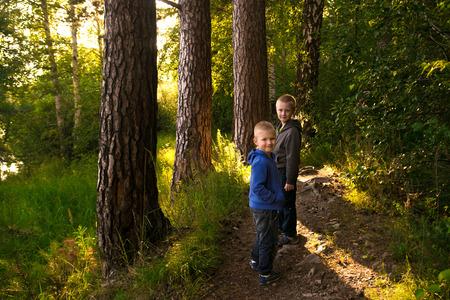 campamento: Ni�os (hermanos, amigos) a pie, senderismo en el bosque de verano verde salvaje