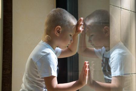 Verdrietig boos wachten saai depressief kind (jongen) in de buurt van een raam, reflectie. Stockfoto