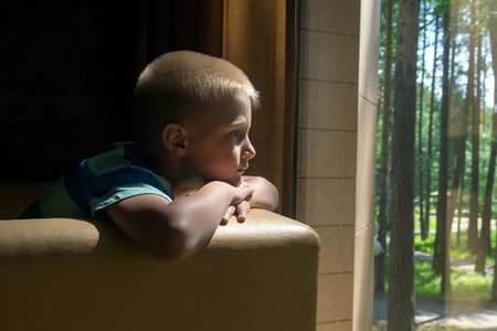 depression: Sad upset waiting boring depressed child (boy) near a window