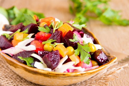 Beet salad. Russian beetroot salad (vinegrette) with beetroot, potato, carrot, peas, cabbage and parsley over rustic wooden table. Banque d'images