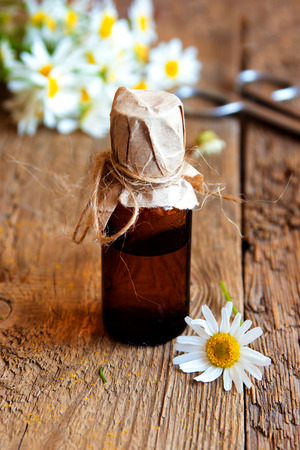 cosmetics products: Daisies and chamomile essential aroma oil over rustic wooden background