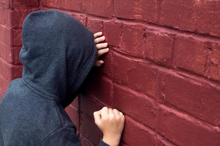 心配して落ち込んで悲しい 10 代の少年 (子) レンガの壁の近くで泣いています。