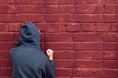 persona deprimida: Preocupado niño deprimido triste adolescente (niño) llorando cerca de la pared de ladrillo