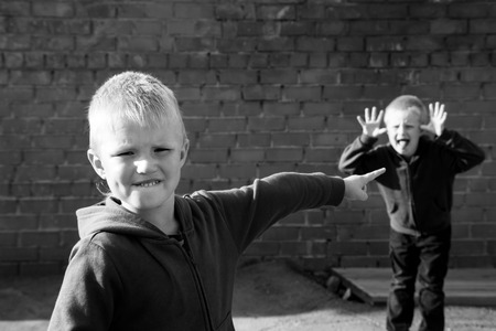sibling rivalry: children quarrel and teasing between two boys (brothers, friends) outdoor near red brick wall