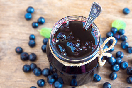 preserve: Blueberry jam in jar with berries and leaves over rustic wooden table