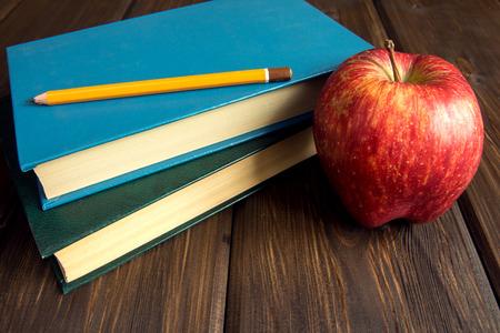 manzana roja: Libros viejos y manzana roja sobre fondo de madera con espacio de copia Foto de archivo
