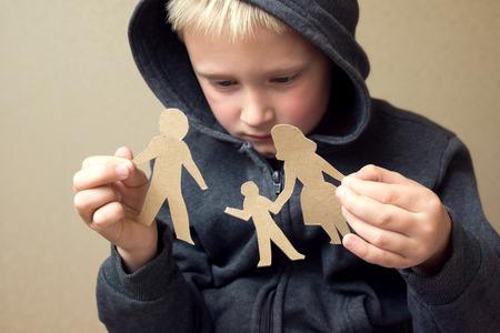 kinderschoenen: Verward kind met gebroken papier familie, problemen, echtscheiding, voogdij, lijden begrip