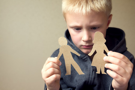 sad cartoon: Confused child with cutting paper parents, family problems, divorce, custody battle, suffer concept Stock Photo