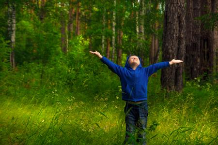 respiracion: Poco feliz hermoso niño sonriente (niño) caminar y divertirse en el bosque verde (parque) y respirar aire fresco