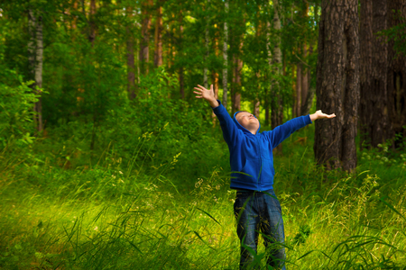 Handsome little happy smiling child (boy) walking and having fun in the green forest (park) and breathing fresh air 免版税图像