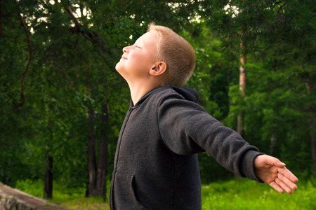 pranayama: Child practice fitness and pranayama (deep breathing exercises) in the forest (park)