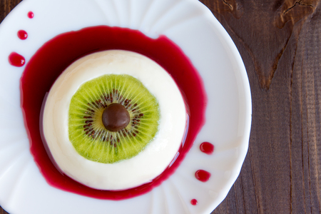 background food: Halloween dessert, bloody eye from vanilla panna cotta and kiwi with berry syrup Stock Photo