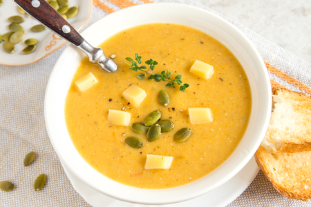 pumpkin soup: Pumpkin cream soup with pumpkin seeds, cheese and herbs in bowl on rustic white table Stock Photo
