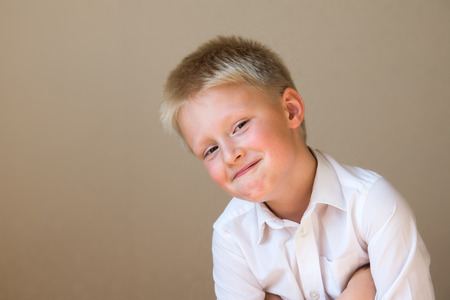 pretender: cunning sly smiling happy smart child boy on gray background Stock Photo