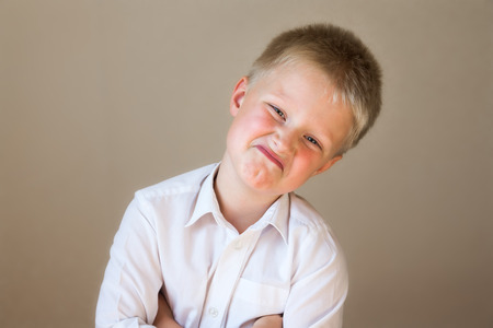 mistrust: Arrogant incredulous funny child (boy) posing in white shirt over gray background Stock Photo