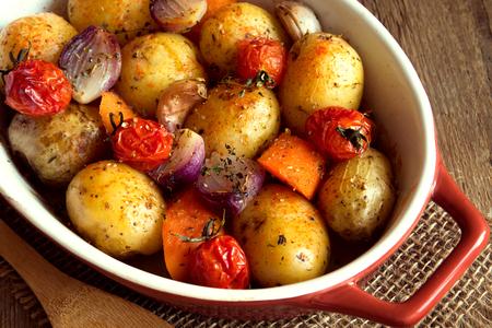 Rustieke oven gebakken groenten met specerijen en kruiden in de ovenschaal close-up, vegetarische organische herfst maaltijd Stockfoto