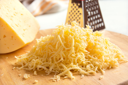 queso rayado: Grated cheese on wooden cutting board