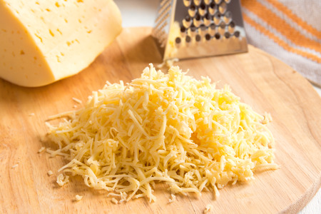 Grated cheese on wooden cutting board