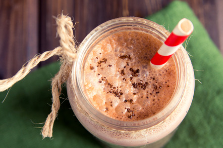 brown background: Chocolate smoothie (milkshake) with straw in jar on dark wooden table