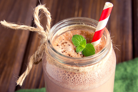 Chocolate smoothie (milkshake) with mint and straw in jar on dark wooden table Banque d'images