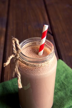Chocolade smoothie (milkshake) met stro in pot op donkere houten tafel