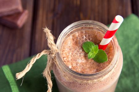 Chocolat Smoothie (milk-shake) à la menthe et de la paille dans un bocal sur la table en bois foncé