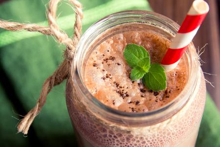 Chocolade smoothie (milkshake) met munt en stro in pot op donkere houten tafel