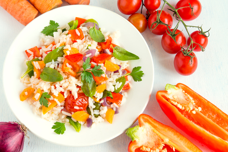 Vegetarian risotto with white rice and fresh colourful vegetables on plate and organic ingredients close up